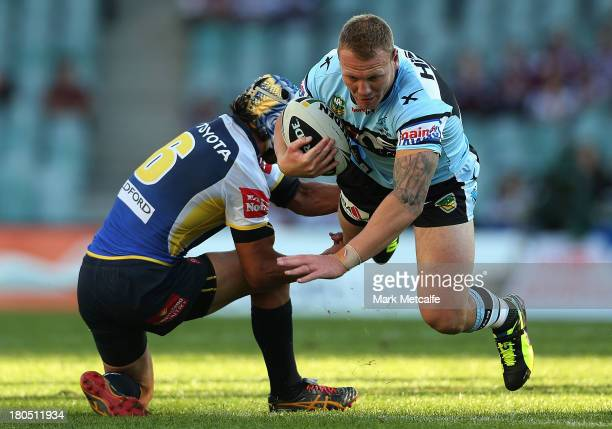 Luke Lewis of the Sharks is tackled by Johnathan Thurston of the Cowboys during the NRL Elimination Final match between the Cronulla Sharks and the...