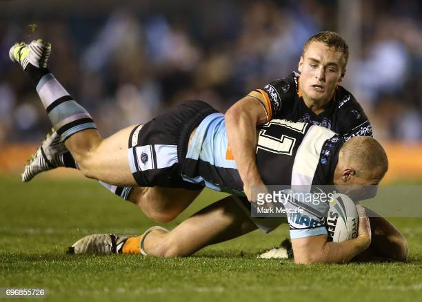 Luke Lewis of the Sharks is tackled during the round 15 NRL match between the Cronulla Sharks and the Wests Tigers at Southern Cross Group Stadium on...