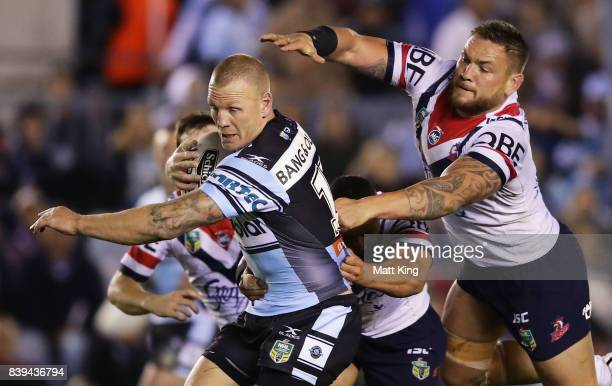Luke Lewis of the Sharks is tackled from behind by Jared WaereaHargreaves of the Roosters during the round 25 NRL match between the Cronulla Sharks...