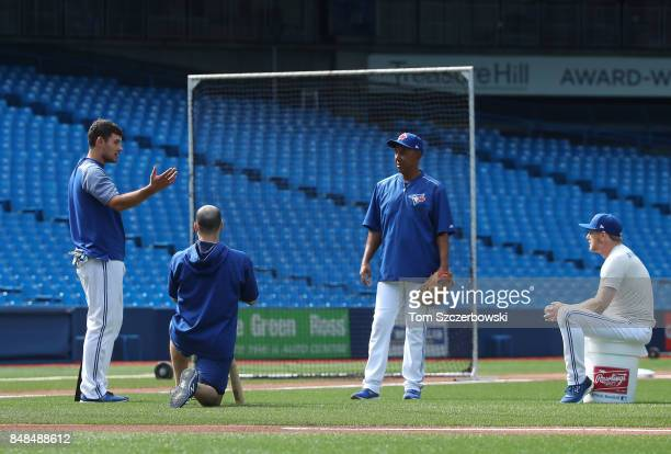 Luke Maile of the Toronto Blue Jays and Raffy Lopez in a training session with first base coach Tim Leiper before the start of MLB game action...