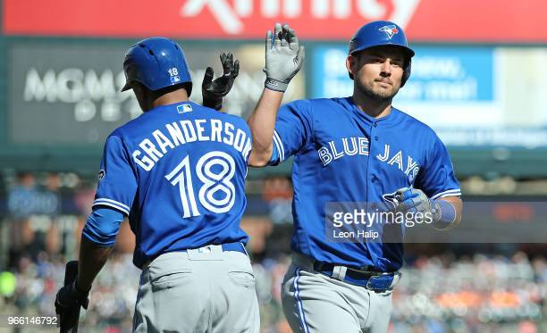 Luke Maile of the Toronto Blue Jays celebrates a solo home run with teammate Curtis Granderson during the fifth inning of the game against the...