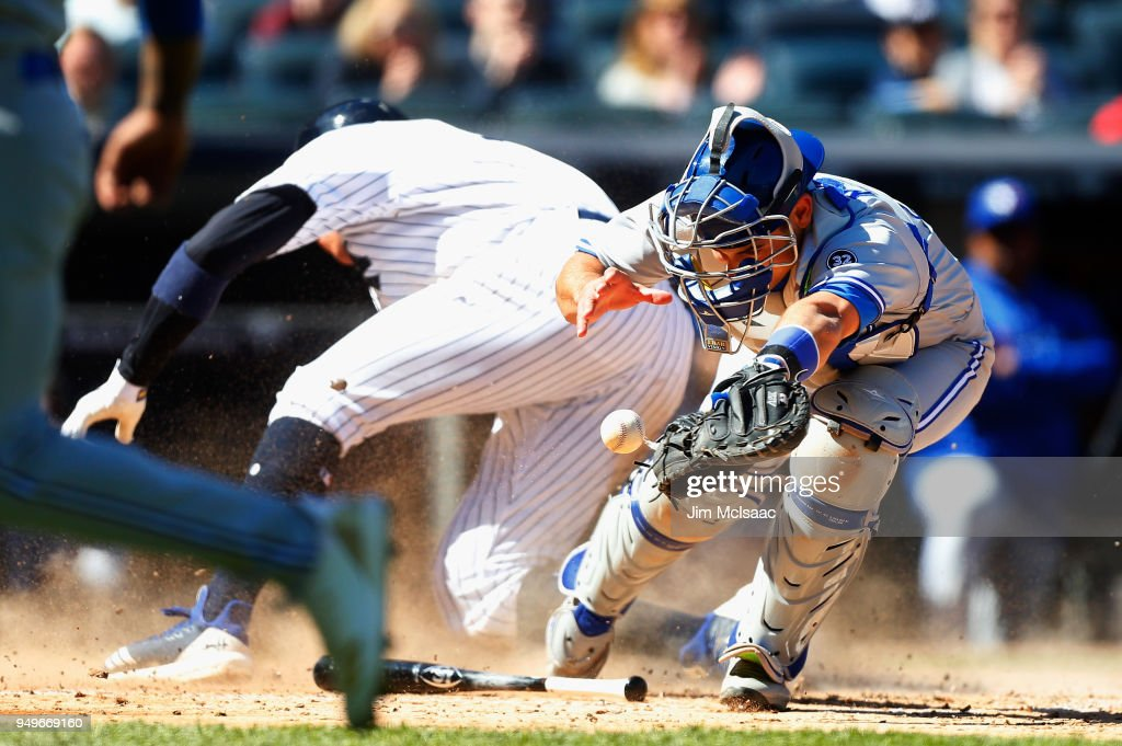 Luke Maile #21 of the Toronto Blue Jays commits a fielding error as he can't hold onto the ball as Aaron Judge #99 of the New York Yankees scores in the sixth inning at Yankee Stadium on April 21, 2018 in the Bronx borough of New York City.