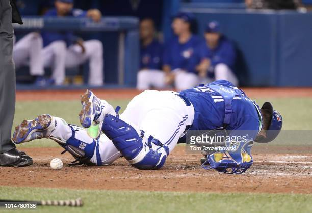 Luke Maile of the Toronto Blue Jays falls to the ground after taking a bounced pitch in the throat in the ninth inning during MLB game action against...