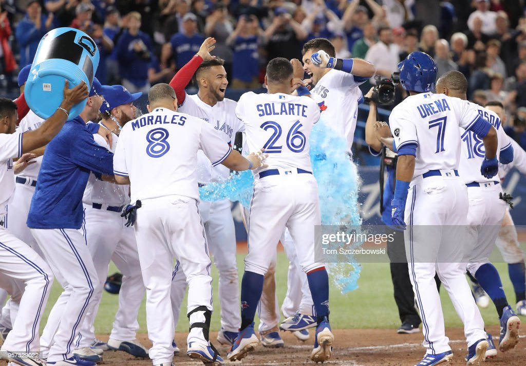 Luke Maile #21 of the Toronto Blue Jays is congratulated at home plate by teammates after hitting a game-winning two-run home run in the twelfth inning during MLB game action against the Boston Red Sox at Rogers Centre on May 11, 2018 in Toronto, Canada.