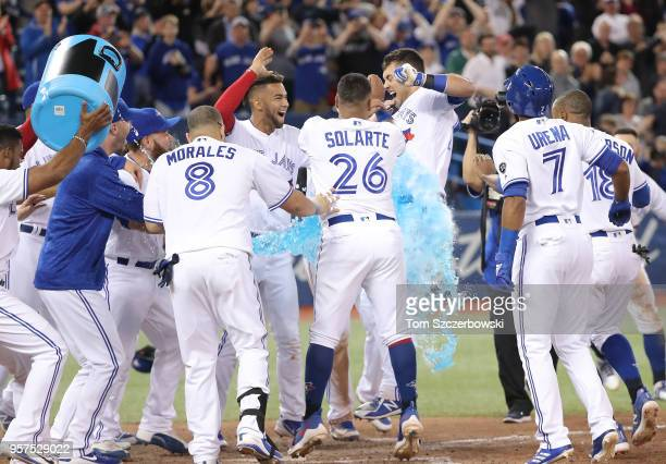 Luke Maile of the Toronto Blue Jays is congratulated at home plate by teammates after hitting a gamewinning tworun home run in the twelfth inning...