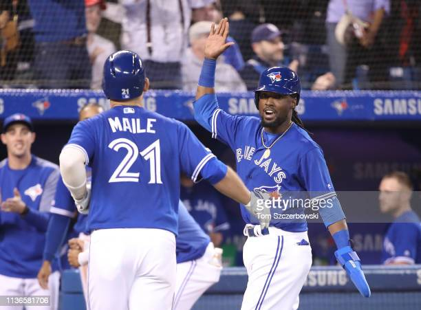 Luke Maile of the Toronto Blue Jays is congratulated by Alen Hanson after hitting a tworun home run in the seventh inning during MLB game action...