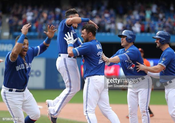 Luke Maile of the Toronto Blue Jays is congratulated by Gio Urshela and teammates after drawing a basesloaded RBI walk to drive in the gamewinning...