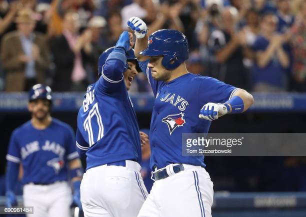 Luke Maile of the Toronto Blue Jays is congratulated by Ryan Goins after hitting a tworun home run in the fifth inning during MLB game action against...