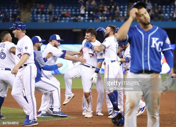 Luke Maile of the Toronto Blue Jays is congratulated on his gamewinning RBI single by Kevin Pillar and Russell Martin and teammates in the tenth...