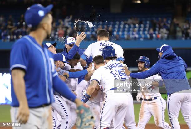 Luke Maile of the Toronto Blue Jays is congratulated on his gamewinning RBI single by teammates in the tenth inning during MLB game action against...