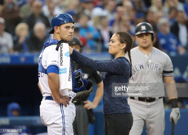 Luke Maile of the Toronto Blue Jays is examined by head athletic trainer Nikki Huffman after taking a foul ball straight back off his mask in the...