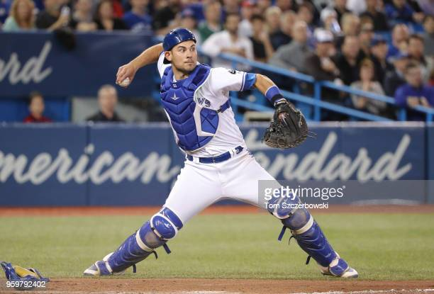 Luke Maile of the Toronto Blue Jays makes a threebase throwing error as he throws the ball away to first base in the fourth inning during MLB game...