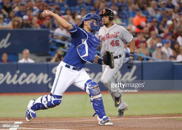 Luke Maile of the Toronto Blue Jays turns a double as he gets the force out at home plate with the bases loaded in the first inning during MLB game...