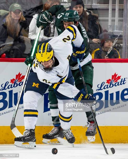 Luke Martin of the Michigan Wolverines battles for the puck with Brennan Sanford of the Michigan State Spartans during the consolation game of the...