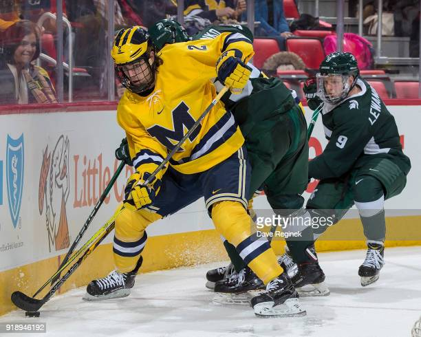 Luke Martin of the Michigan Wolverines battles for the puck with Patrick Khodorenko and Mitchell Lewandowski of the Michigan State Spartans during...