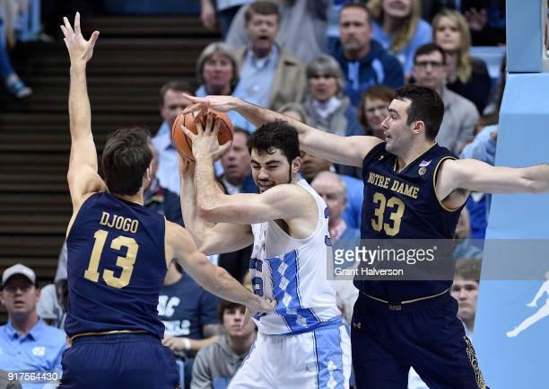 Luke Maye of the North Carolina Tar Heels battles Nikola Djogo and John Mooney of the Notre Dame Fighting Irish for a rebound during their game at...