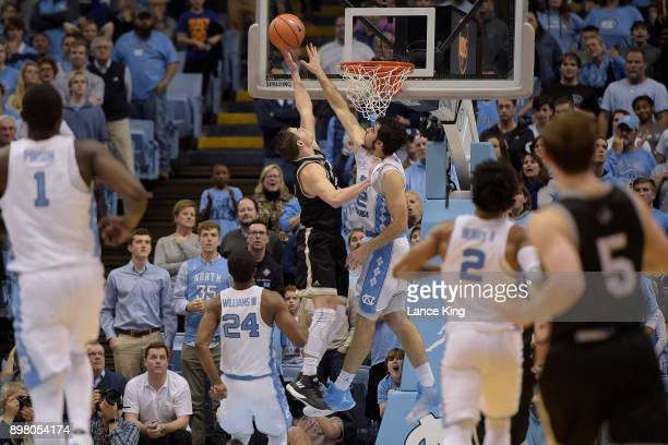 Luke Maye of the North Carolina Tar Heels defends shot by Fletcher Magee of the Wofford Terriers at Dean Smith Center on December 20 2017 in Chapel...