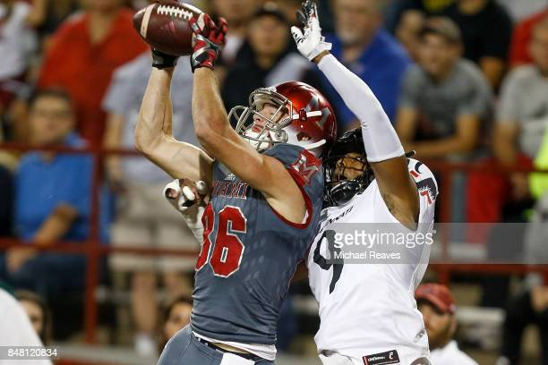 Luke Mayock of the Miami Ohio Redhawks catches a touchdown defended by Linden Stephens of the Cincinnati Bearcats during the first half at Yager...