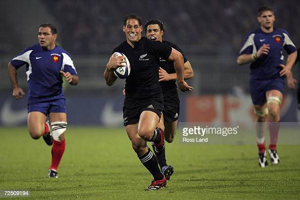 Luke McAlister of New Zealand breaks through the French defence to score a try during the International rugby match between France and New Zealand at...