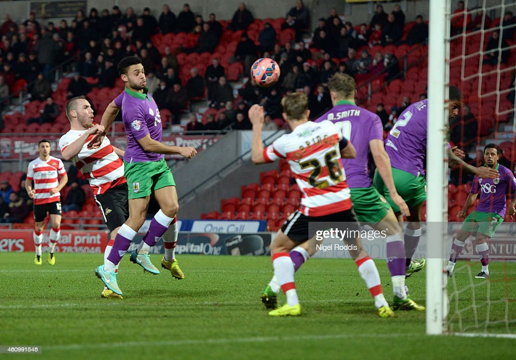 Luke McCullough (L) of Doncaster Rovers shoots to score during the FA Cup Third Round match between Doncaster Rovers and Bristol City at Keepmoat Stadium on January 3, 2015 in Doncaster, England.