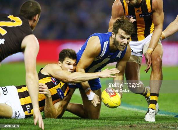 Luke McDonald of the Kangaroos handballs from Jaeger O'Meara of the Hawks during the round five AFL match between the North Melbourne Kangaroos and...