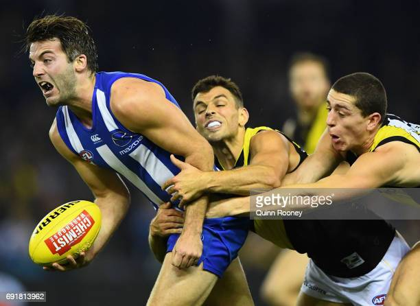 Luke McDonald of the Kangaroos handballs whilst being tackled by Sam Lloyd and Jason Castagna of the Tigers during the round 11 AFL match between the...
