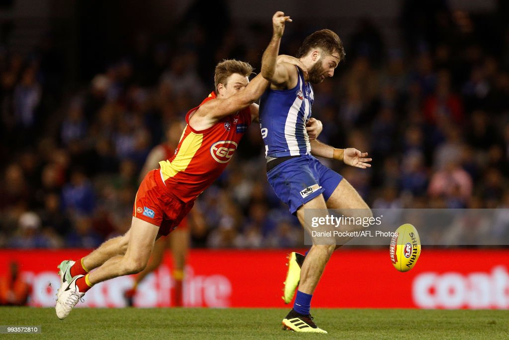 Luke McDonald of the Kangaroos kicks the ball whilst being tackled during the round 16 AFL match between the North Melbourne Kangaroos and the Gold Coast Titans at Etihad Stadium on July 8, 2018 in Melbourne, Australia.