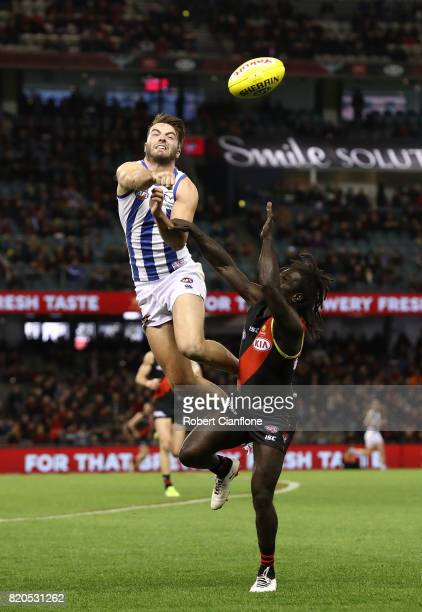 Luke McDonald of the Kangaroos punches the ball away from Anthony McDonald-Tipungwuti of the Bombers during the round 18 AFL match between the...