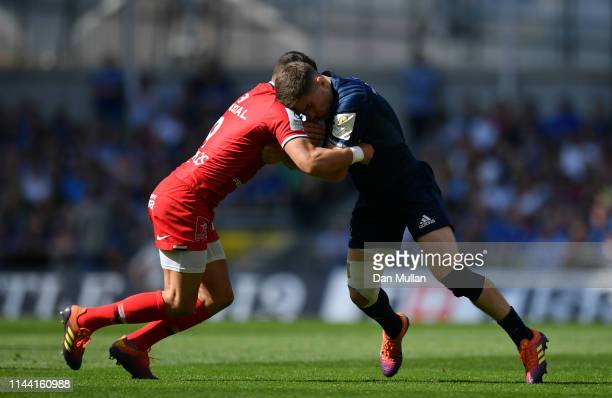 Luke McGrath of Leinster is tackled by Sebastien Bezy of Toulouse during the Heineken Champions Cup Semi Final match between Leinster Rugby and...