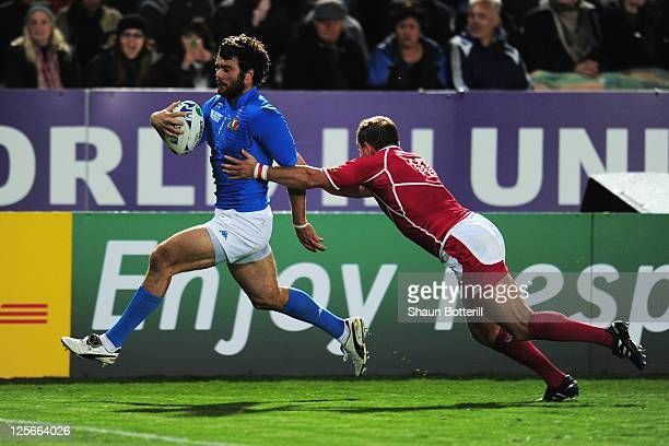 Luke McLean of Italy scores their seventh try despite the challenge of Konstantin Rachkov of Russia during the IRB 2011 Rugby World Cup Pool C match...