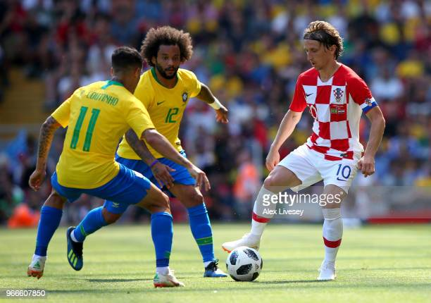 Luke Modric of Croatia is challenged by Marcelo of Brazil and Philippe Coutinho of Brazil during the International Friendly match between Croatia and...