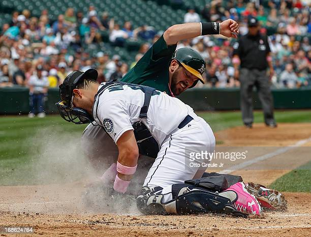 Luke Montz of the Oakland Athletics is tagged out at the plate by catcher Jesus Montero of the Seattle Mariners while trying to score on a fielders...
