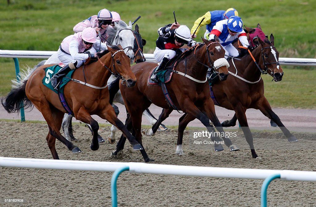 Luke Morris riding Venus Grace (C, black) win The Racing Welfare handicap Stakes at Lingfield racecourse on March 30, 2016 in Lingfield, England.