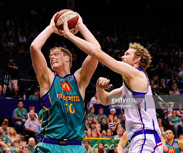 Luke Nevill of the Crocodiles contests the ball with Luke Schenscher of the 36ers during the round 12 NBL match between the Townsville Crocodiles and...