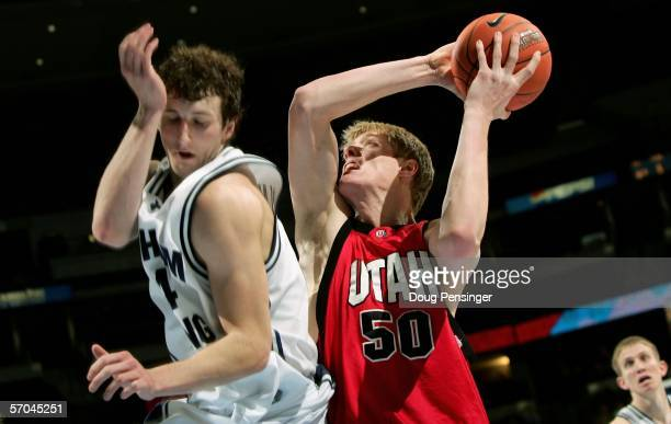 Luke Nevill of the Utah Runnin' Utes shoots as Trent Plaisted of the Brigham Young University Cougars avoids fouling him during the Mountain West...