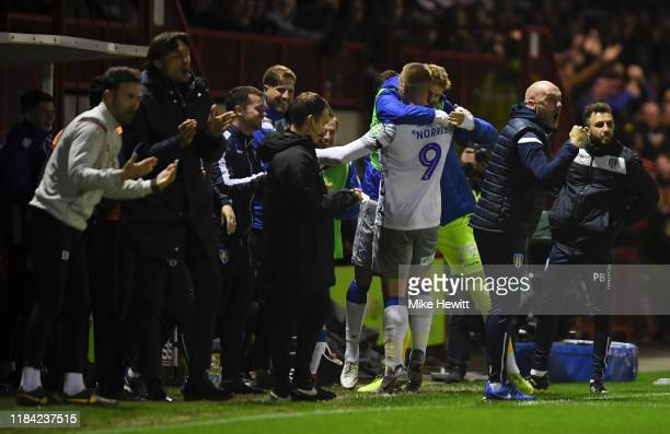 Luke Norris of Colchester United celebrates after scoring his team's first goal with his team mates during the Carabao Cup Round of 16 match between...
