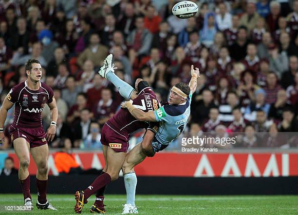 Luke O'Donnell of the Blues is tackled by Johnathan Thurston of the Maroons during game two of the ARL State of Origin Series between the New South...