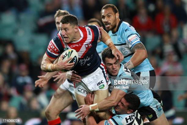 Luke O'Donnell of the Roosters is tackled during the round 19 NRL match between the Sydney Roosters and the Cronulla Sharks at Allianz Stadium on...