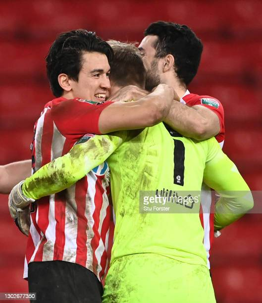 Luke O'Nien congratulates Lee Burge of Sunderland after their side win the penalty shoot out during the Papa John's Trophy Semi-Final match between...