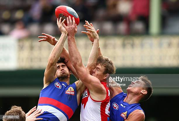 Luke Parker of the Swans competes for the ball against Easton Wood and Michael Talia of the Bulldogs during the round five AFL match between the...