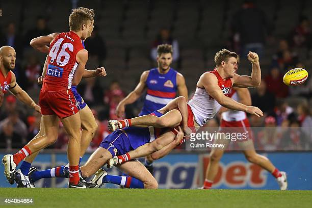 Luke Parker of the Swans handballs whilst being tackled by Ayce Cordy of the Bulldogs during the round 22 AFL match between the Western Bulldogs and...