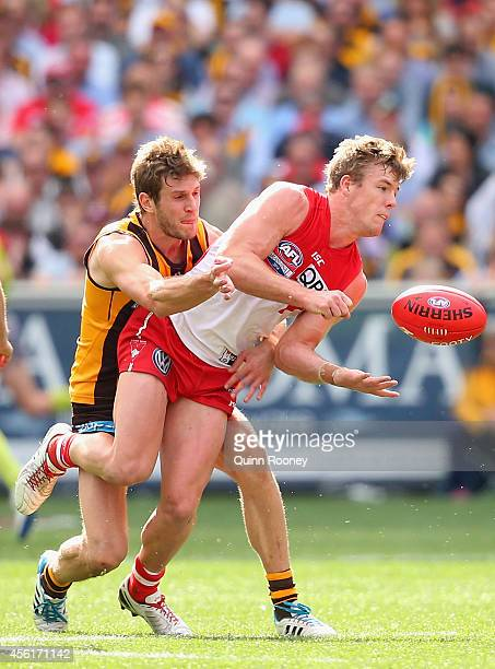 Luke Parker of the Swans handballs whilst being tackled by Grant Birchall of the Hawks during the 2014 AFL Grand Final match between the Sydney Swans...