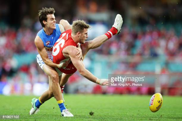 Luke Parker of the Swans is tackled by Jack Bowes of the Suns during the round 16 AFL match between the Sydney Swans and the Gold Coast Suns at...