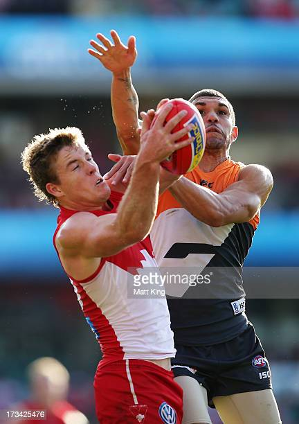 Luke Parker of the Swans mark in front of Curtly Hampton of the Giants during the round 16 AFL match between the Sydney Swans and the Greater Western...