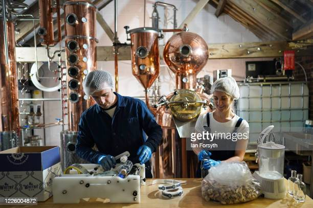Luke Pentith and Jessica Slater prepare a new batch of sanitising hand rub at the Whitby Gin distillery on May 20, 2020 in York, United Kingdom. The...