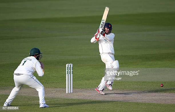 Luke Procter of Lancashire hits out with Brendan Taylor of Nottinghamshire looking on during day one of the Specsavers County Championship Division...