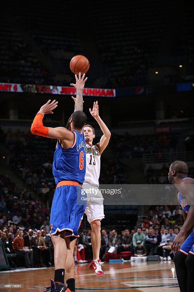 Luke Ridnour #13 of the Milwaukee Bucks shoots against Tyson Chandler #6 of the New York Knicks on February 3, 2014 at the BMO Harris Bradley Center in Milwaukee, Wisconsin.