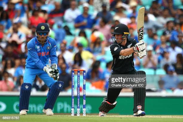 Luke Ronchi of New Zealand hits out while India wicket keeper MS Dhoni looks on during the ICC Champions Trophy Warmup match between India and New...