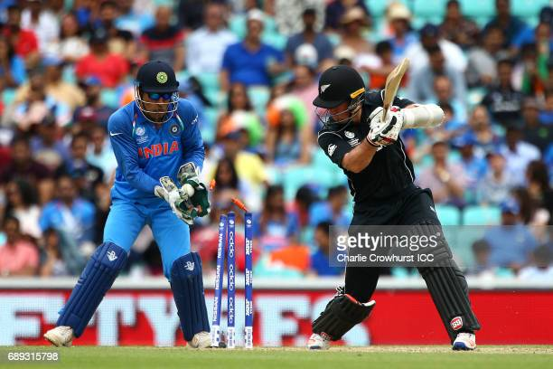 Luke Ronchi of New Zealand looks on with Wicket Keeper MS Dhoni after being bowled out by Ravindra Jadeja of India during the ICC Champions Trophy...