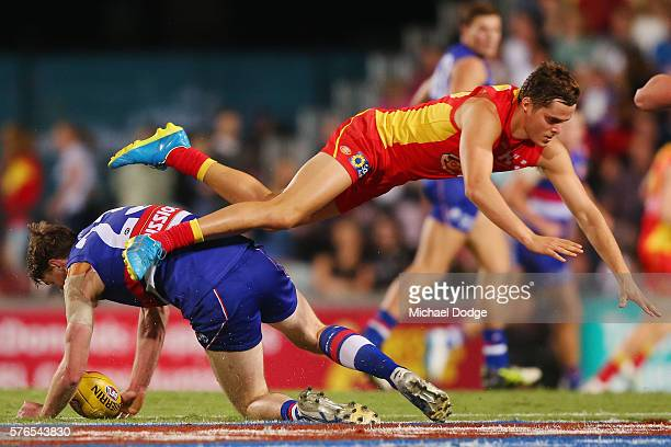 Luke Russell of the Suns tumbles over Jordan Roughead of the Bulldogs during the round 17 AFL match between the Western Bulldogs and the Gold Coast...